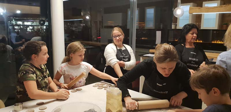Eifriges Backen im Küchen - Raumdesign Studio Griessner